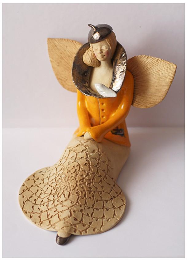 Anioł w żółtym kubraczku z ptakiem na kołnierzu